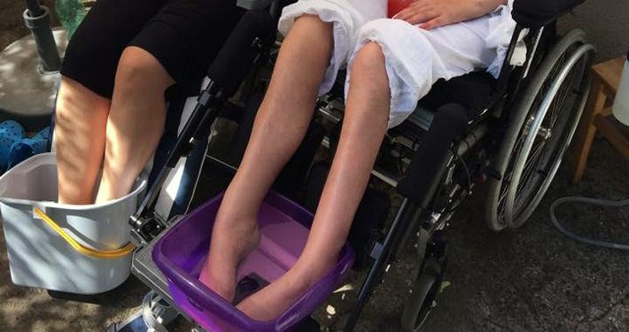 Fußbad bei heißem Wetter von Patientin im Rollstuhl