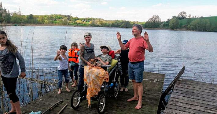 Rollstuhlfahrer mit Familie auf einem Holzsteg.