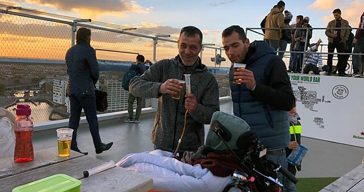 Rollstuhlfahrer auf Roof Bar, Bier genießend