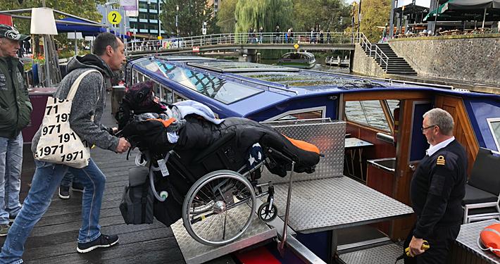 Rollstuhlfahrerin beim Einfahren auf ein Ausflugsboot.
